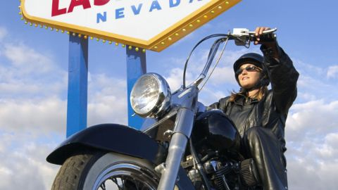 Woman riding motorcycle by Las Vegas sign.