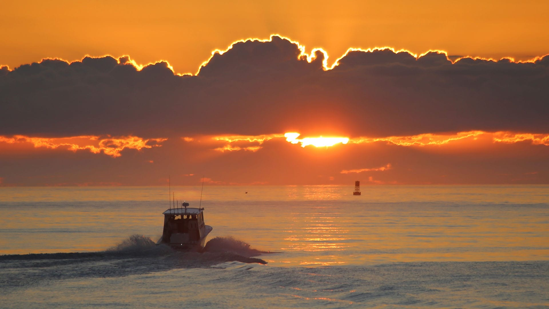 A boat heads out to the Atlantic Ocean as the sun rises at Port Canaveral.