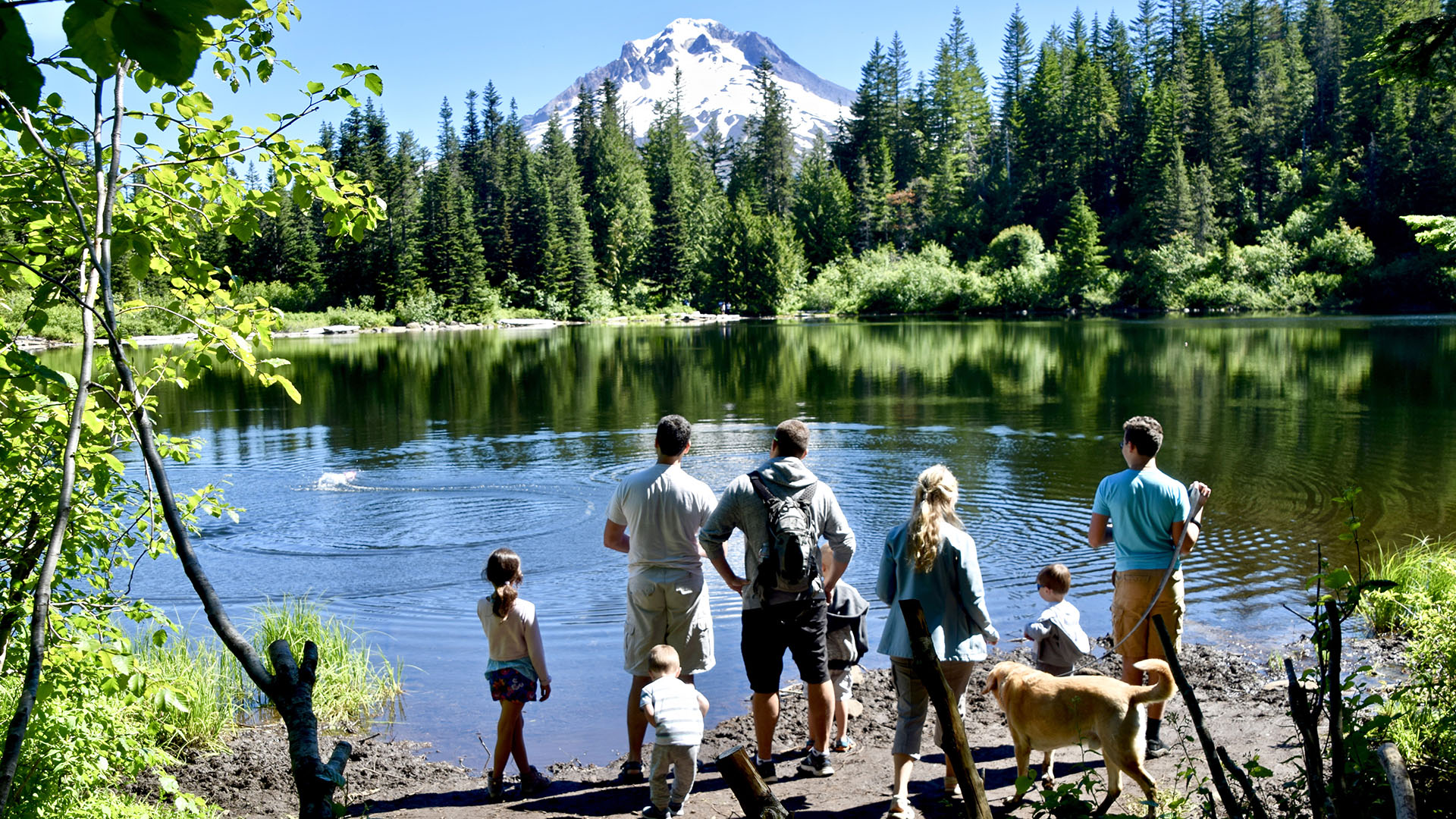 A family skips rocks in Mirror Lake, disrupting the reflection of Mt. Hood.