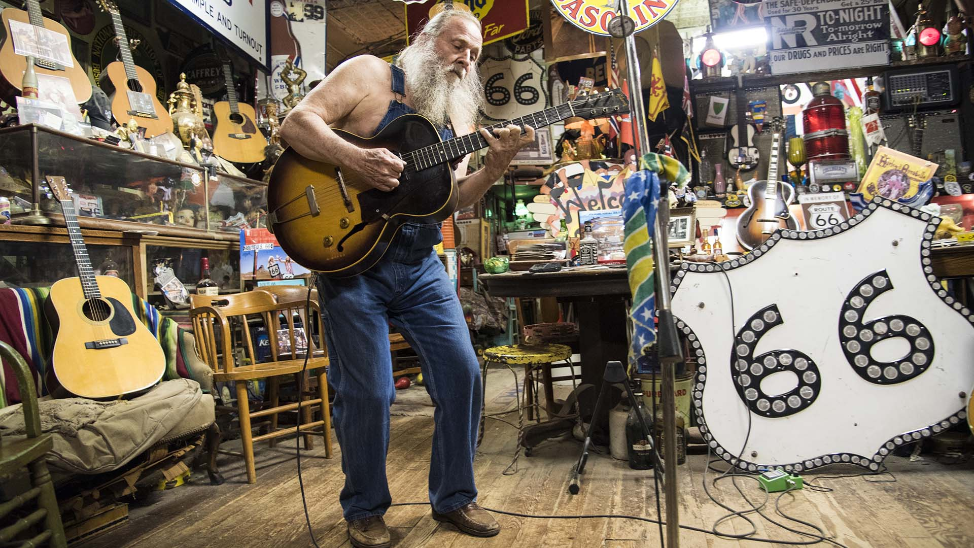Harly Russell, the one-of-a-kind owner of the Sandhills Curiosity Shop in Erick, Oklahoma, plays guitar for visitors.