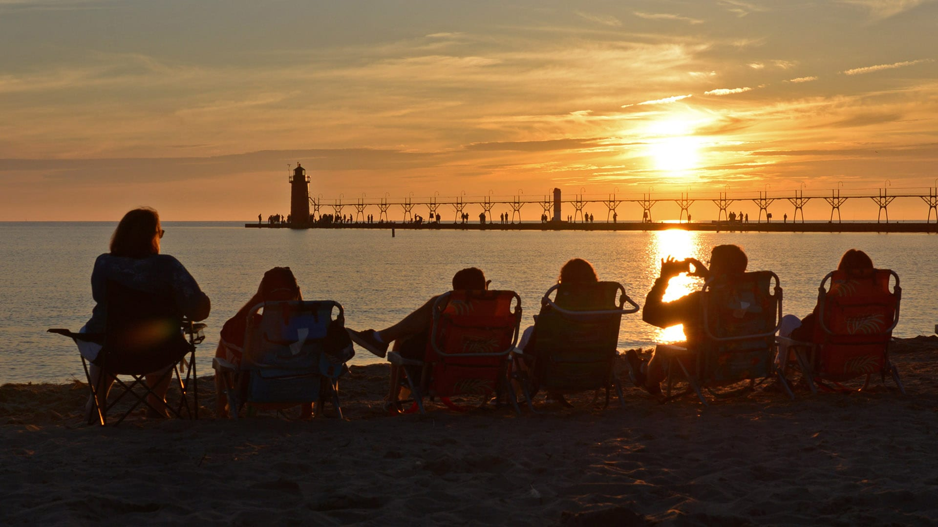 People watch the sun set near the historic lighthouse in South Haven, Michigan.
